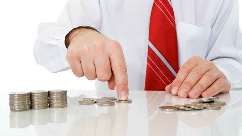 Geschäftsmann sitzt am Tisch und zählt Geldmünzen