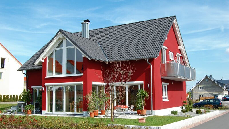 Rotes, modernes Einfamilienhaus mit großen Fenstern