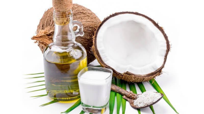Kokosölflasche, Kokosmilchglas und Löffel mit Kokosraspeln neben Kokosnüssen vor weißem Hintergrund