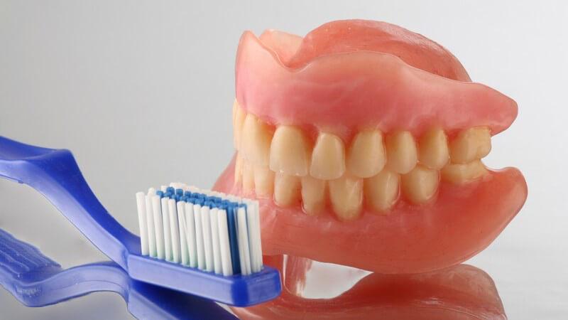Gebiss mit gelblichen Zähnen neben blauer Zanbürste auf Spiegeluntergrund