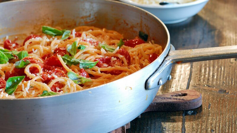 Nahaufnahme Spaghetti mit frischen Tomaten in Pfanne, daneben Parmesan