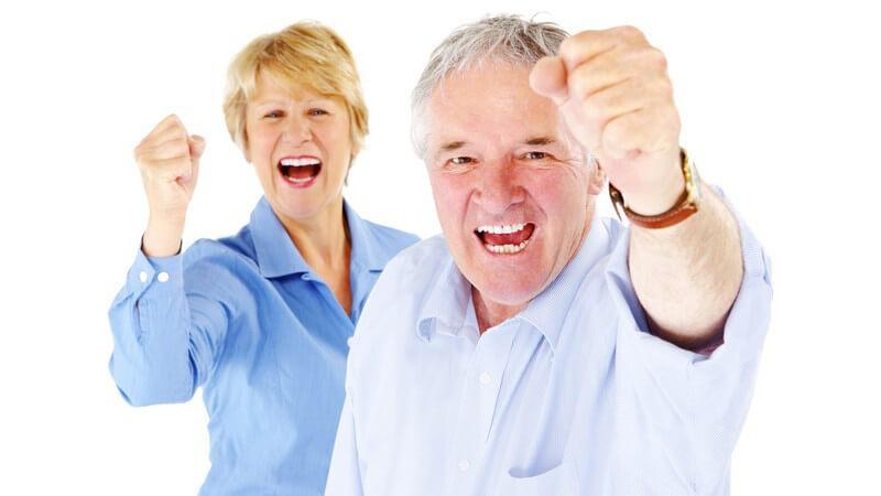 Älteres Paar hält Fäuste als Zeichen von Erfolg in Kamera