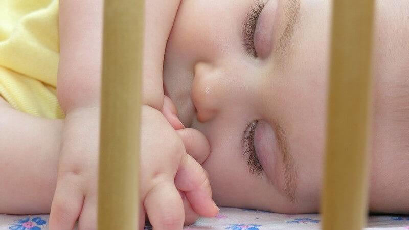 Säugling schläft in Babybett
