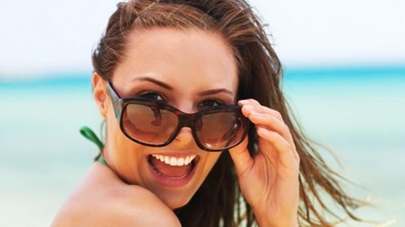 Gesicht einer jungen, braunhaarigen Frau in Bikini am Strand mit Sonnenbrille und offenem Mund