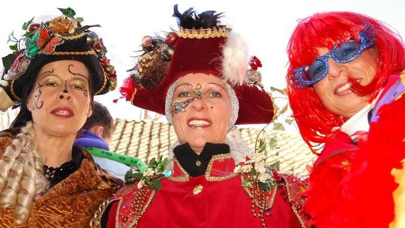 Drei reife jecke Frauen in Karnevalskostümen mit roter Perücke, Schminke, Hüten, Federn, Federboas