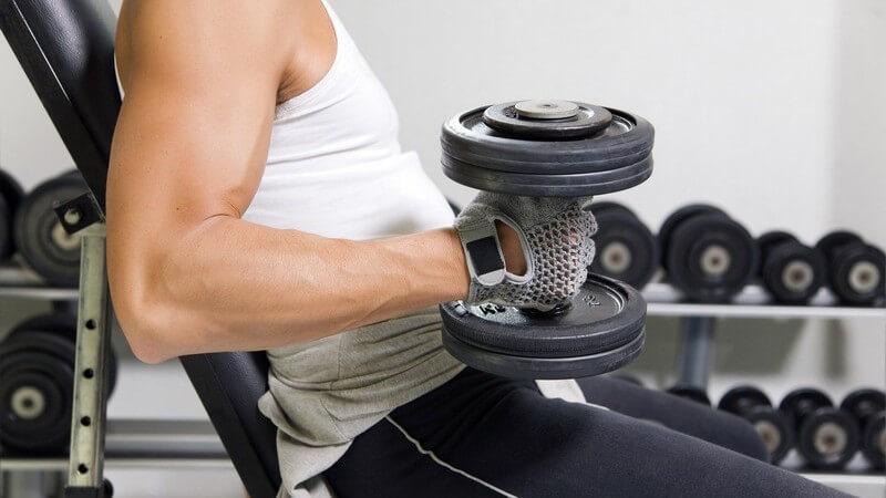 Muskulöser Mann in weißem Shirt sitzt auf der Trainingsbank und macht Hanteltraining