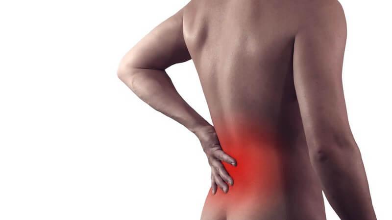 Rückenschmerzen - Nackter Mann fasst sich an den rot hervorgehobenen Rücken