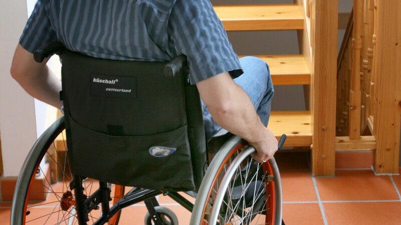 Rückansicht Mann im Rollstuhl vor Treppe