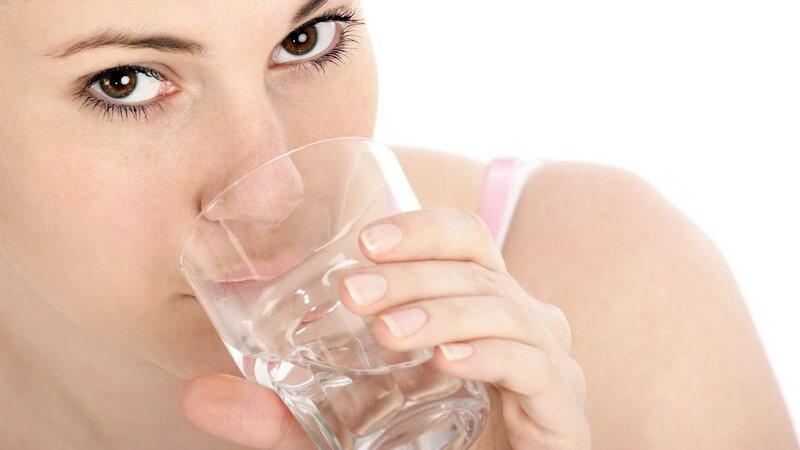 Junge Frau trinkt aus einem Glas Wasser