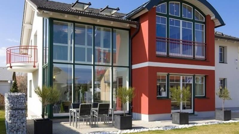 Rotes Haus mit rundem Dach und geradem, gläsernen Anbau, Sitzgruppe auf der Veranda