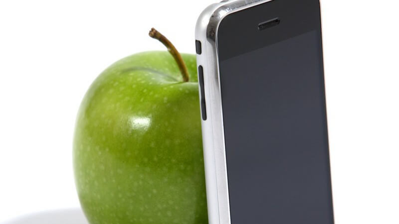 Grüner, frischer Apfel neben Rückseite eines Handys auf weißem Hintergrund