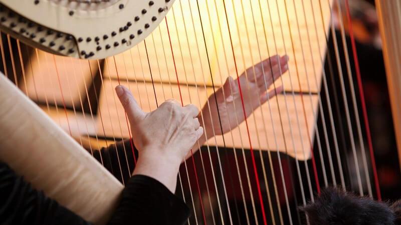 Frau beim Spielen einer großen Harfe in einem Orchester