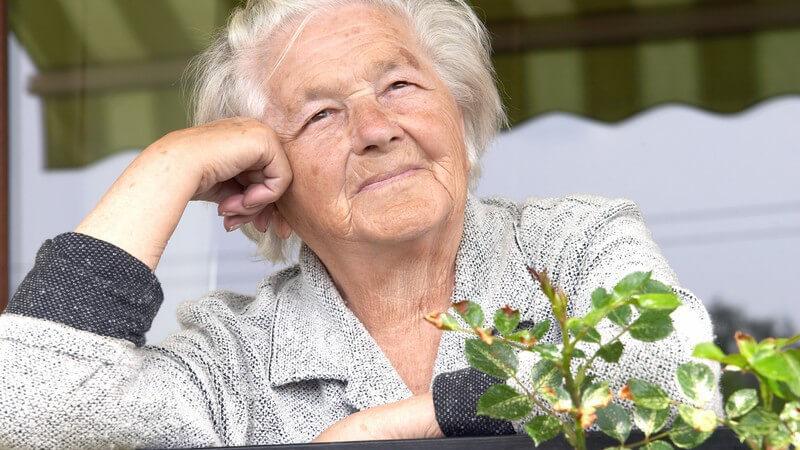 Nahaufnahme alte Frau mit weißen Haaren steht auf Balkon, Kopf auf die Hand gestützt