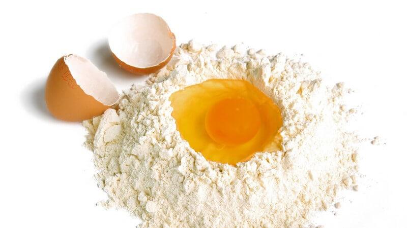 Rohes Ei in Mehlmulde, daneben die Eierschale auf weißem Hintergrund