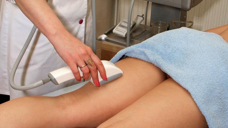 Frau liegt auf Bauch, bekommt Beine mit Laser epiliert