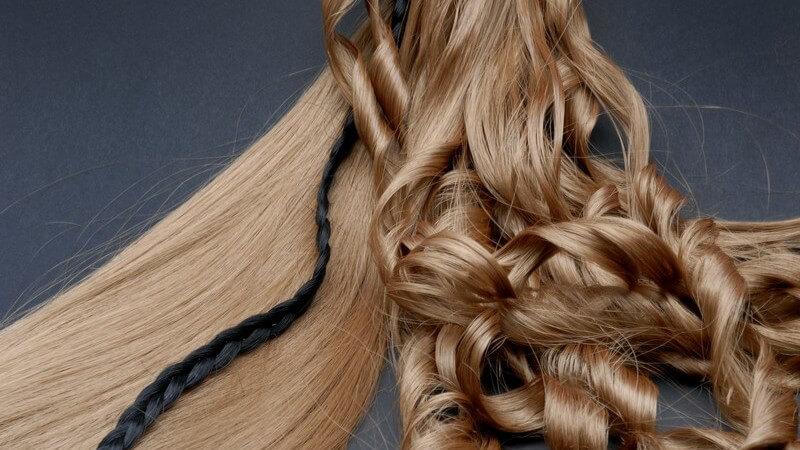 Blonde lange Haare, glatt und gelockt, dazwischen schwarzer dünner geflochtener Zopf