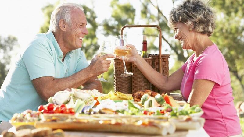 Älteres Paar beim Picknick stößt mit Weingläsern an
