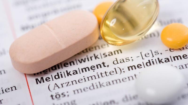 Mehrere Tabletten und Pillen liegen auf Wörterbuch auf Begriff Medikament