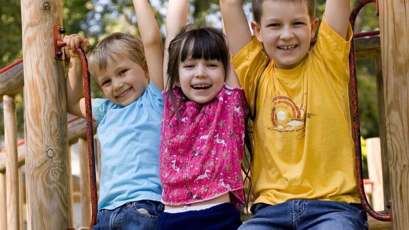 Drei Kinder am Klettergerüst am Spielplatz
