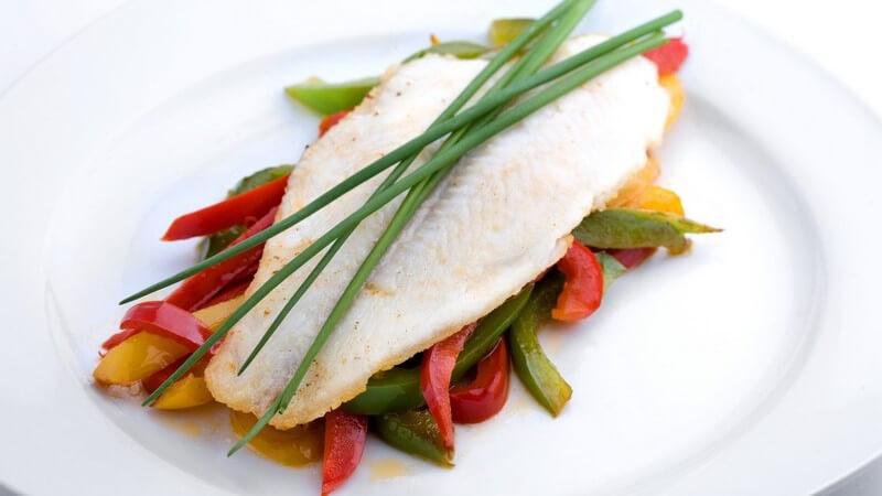 Schön angerichtetes Fischfilet mit Schnittlauch auf buntem Gemüse
