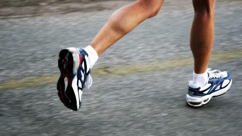 Beine einer Läuferin mit Laufschuhen auf grauem Asphalt