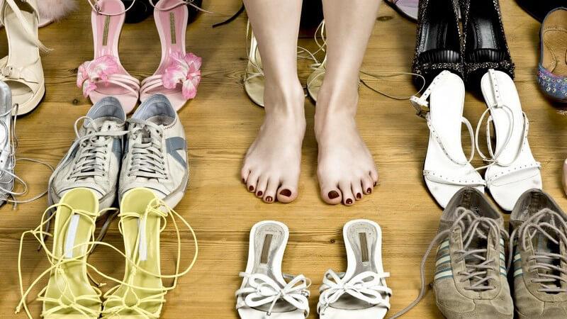 Nackte Frauenfüße auf Holzboden zwischen vielen Schuh-Paaren