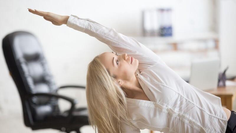Blonde Frau in weißer Bluse macht Fitnessübungen am Arbeitsplatz im Büro, den linken Arm über den Kopf gestreckt