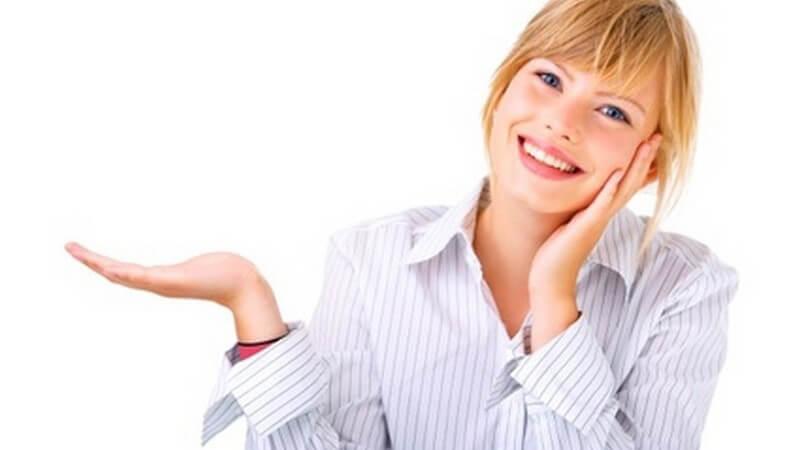 Blonde Frau in weiß-gestreifter Bluse lächelt, hält die Hand präsentierend zur Seite, die andere an der Wange