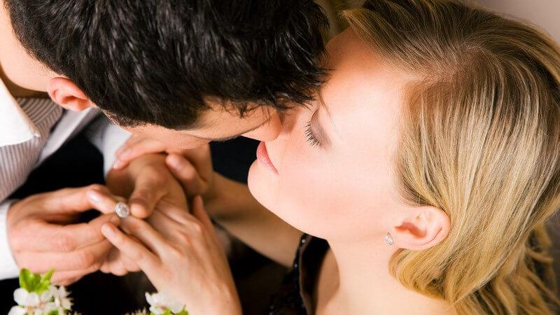 Ansicht von oben: Mann steckt Frau nach Heiratsantrag Finger an, sie küssen sich