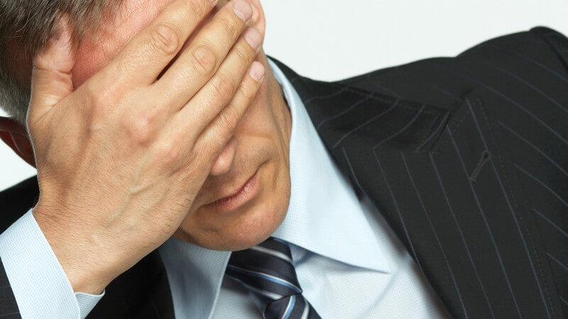 Geschäftsmann hält gestresst Hand vors Gesicht