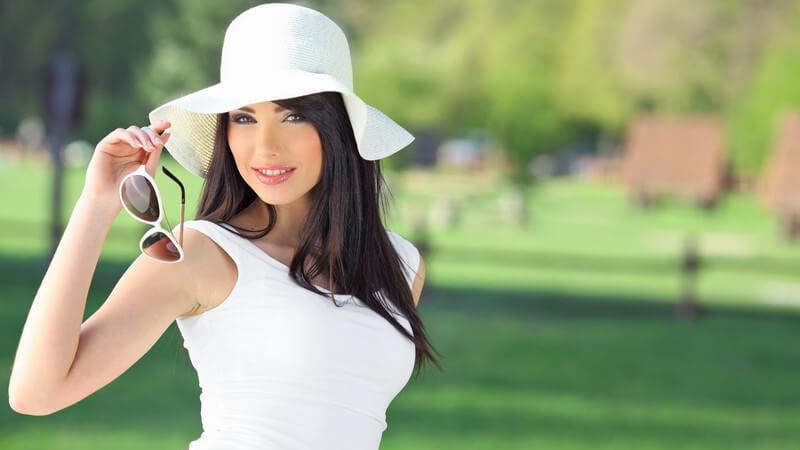 Junge Frau mit Sommerhut und Sonnenbrille in Hand im Park