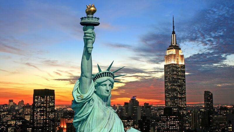 Freiheitsstatue New York, im Hintergrund Sykline am Abend
