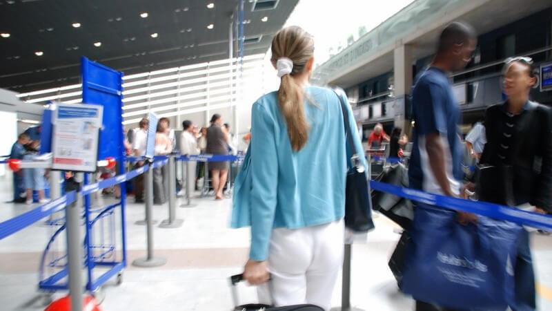 Rückansicht junge Frau zieht Koffer im Flughafen hinter ihr her, umgeben von vielen Menschen