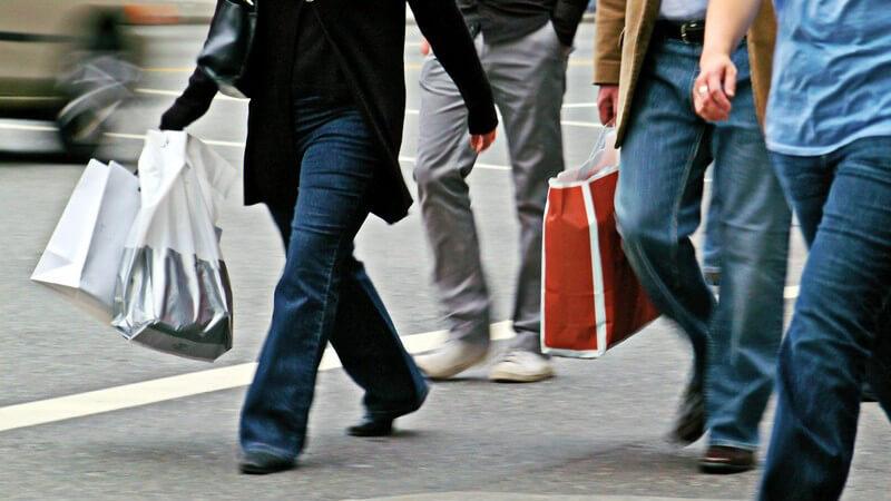 Unterkörper mehrerer Menschen auf Straße mit Einkaufstaschen