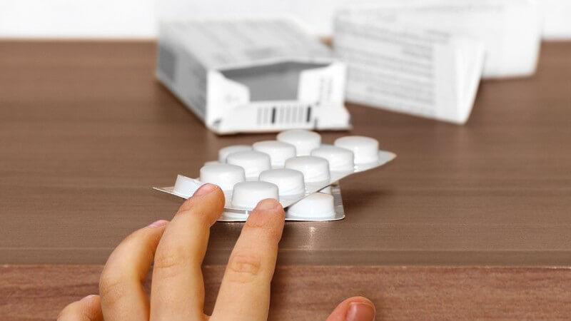 Kinderhand an Medikamentenschachtel, Tabletten