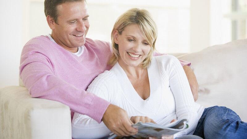 Erwachsenes Paar sitzt lächelnd auf der Couch und blättert in einer Zeitschrift