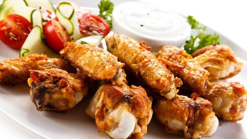 Weißer Teller mit Chicken Wings, Gemüse und weißem Dip