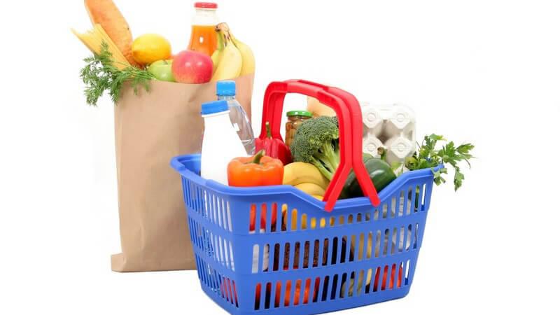 Tüte und Einkaufskorb mit vielen gesunden Lebensmitteln wie Obst und Gemüse