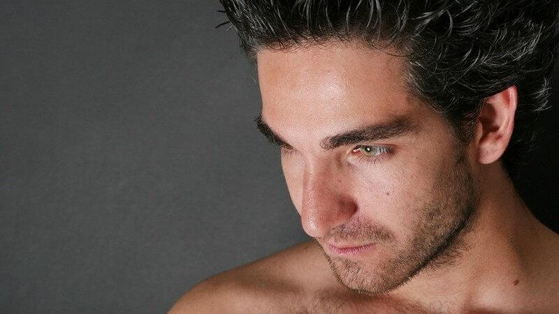 Gesicht und Schulterpartie eines jungen Mannes, schaut nach unten, unbekleidet und dunkelhaarig mit Bart und Brusthaaren