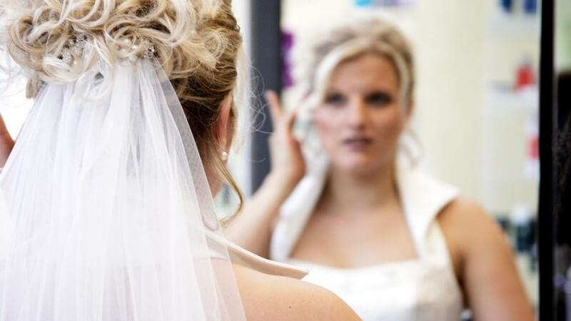 Braut vor Spiegel prüft ihre Frisur