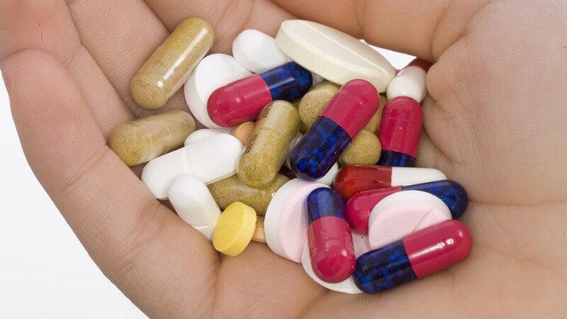 Verschieden farbige Kapseln und Tabletten in offener rechter Hand