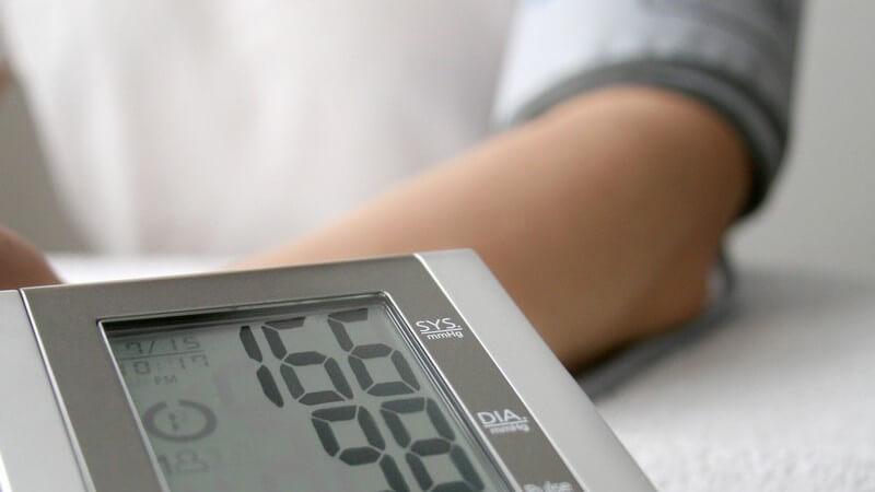 Blutdruckmessgerät, im Hintergrund Patient mit Bluthochdruck