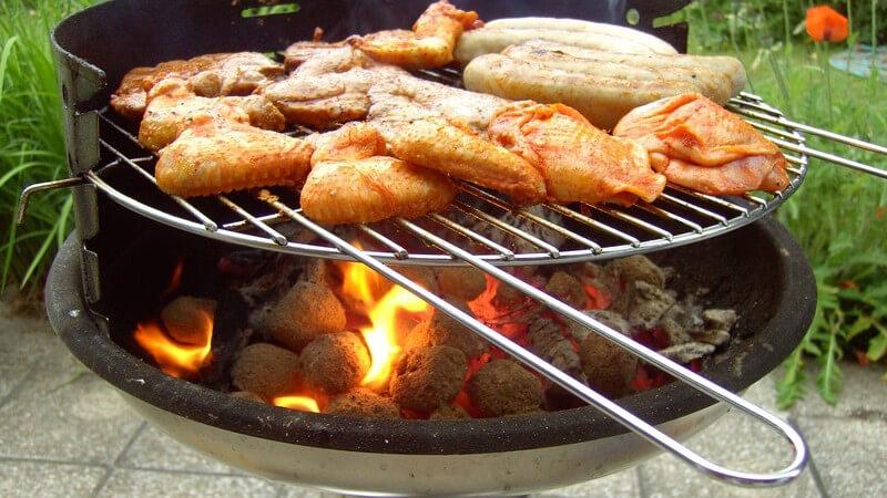 Frisches Fleisch auf Grillrost im Garten