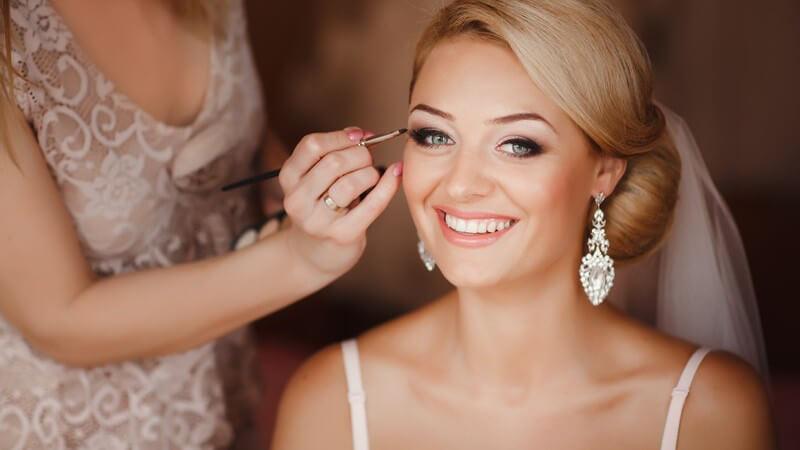Hübsche blonde Braut mit langen Ohrringen wird geschminkt
