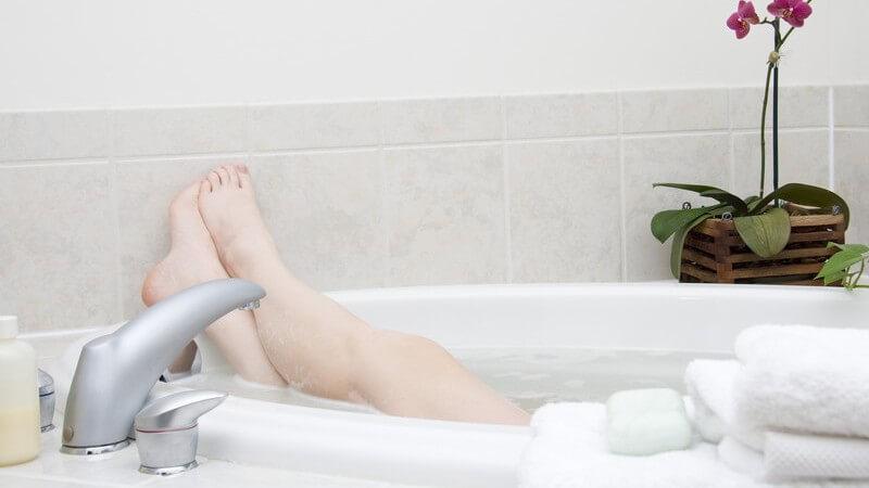 Beine einer Frau schauen aus Badewanne mit viel Schaum raus