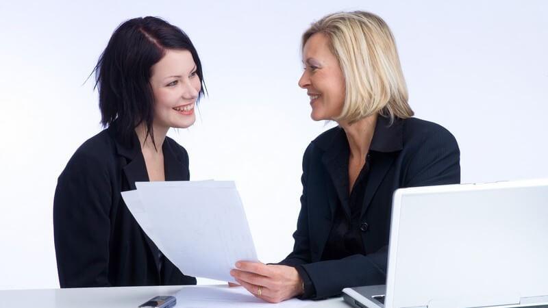 Beruf - Chefin mit weißem Laptop und Papieren im Gespräch mit einer Angestellten