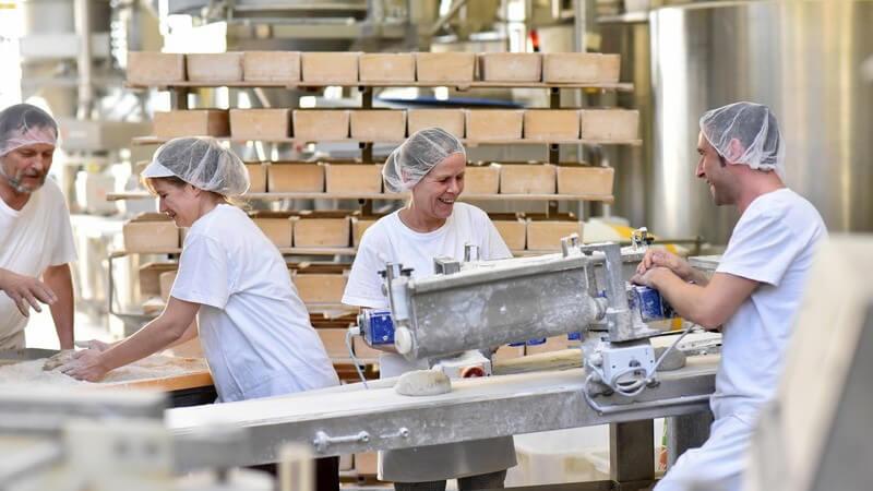 Vier Arbeiter/innen in weißer Arbeitskleidung und Haube in einer Großbäckerei