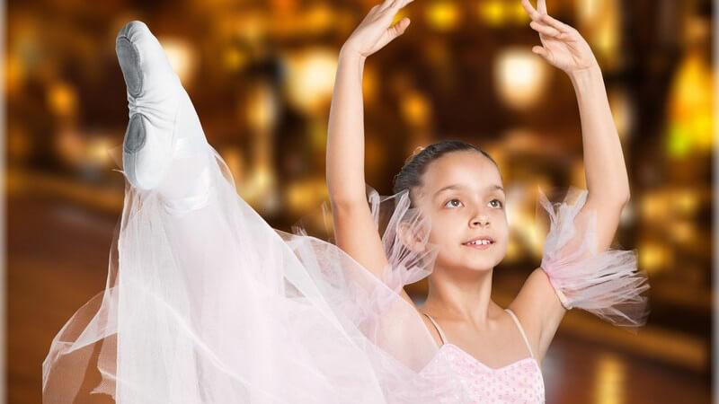 Mädchen in rosa Ballettkleid macht eine Übung mit den Armen über den Kopf und hochgestrecktem Bein