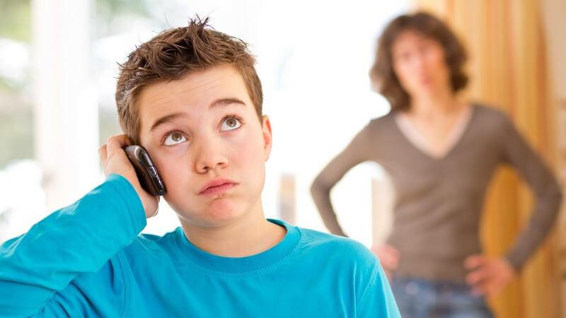 Junge (Pubertät) mit Handy am Ohr, im Hintergrund genervte Mutter