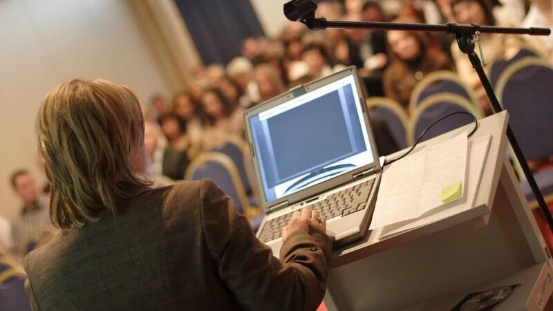 Frau steht mit Laptop vor Podium bei einem Vortrag, in Richtung Publikum fotografiert